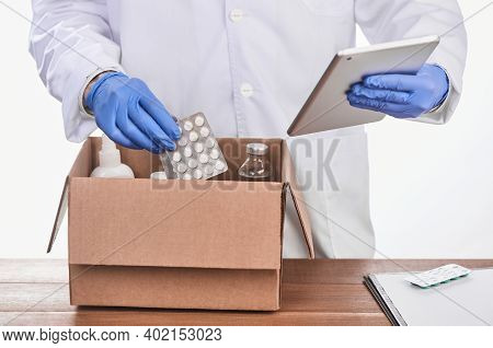 Pharmacist Putting Pills Into A Box And Checking The List On A Tablet Computer