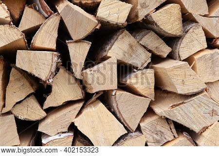 Background From A Stack Of Firewood For Heating A House, Stacked In The Backyard, Uncut Wood, Birch.