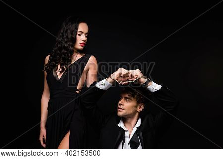 Sexy Woman In Dress Looking At Submissive And Handcuffed Man Isolated On Black