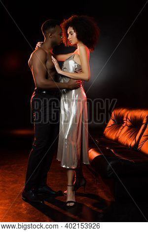 Full Length Of Shirtless African American Man Seducing Woman In Dress Near Couch On Black
