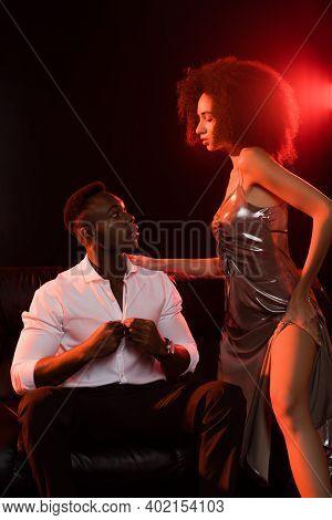African American Woman In Dress Seducing Man In Suit On Black