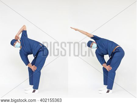 Standing caucasian medical professional in uniform stretching back and arms, rotating body