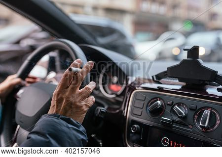 Detail Of Hand Of Old Woman Smoking And Driving A Car. Unsafe And Insane. Smoker