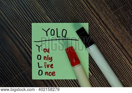 Yolo - You Only Live Once Write On Sticky Notes Isolated On Wooden Table.