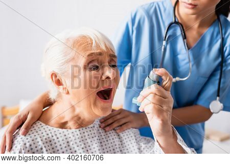Elderly Woman Using Inhaler While Suffering From Asthma Attack Near Nurse Touching Her Shoulders On