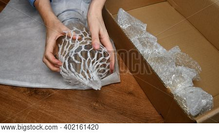 Woman Hands Wrap Fragile Glassware Into Packing Plastic Net In Preparation To Move In New Home. Pack