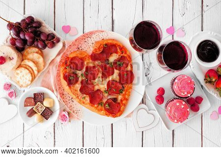 Homemade Valentines Day Dinner. Top View Table Scene On A White Wood Background. Heart Shaped Pizza,