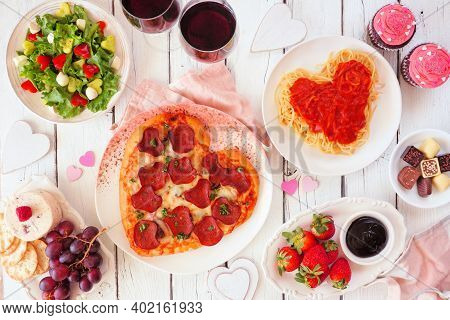 Homemade Valentines Day Dinner. Overhead View Table Scene On A White Wood Background. Heart Shaped P