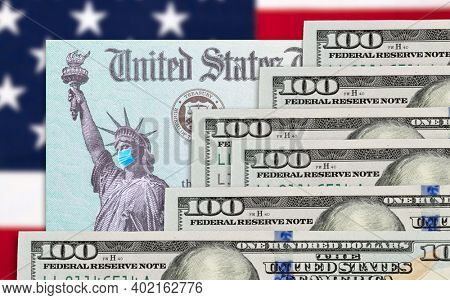 Money and United States IRS Stimulus Check with Statue of Liberty Wearing Face Mask Resting on American Flag.
