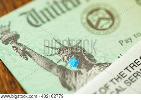 United States IRS Stimulus Check with Statue of Liberty Wearing Medical Face Mask.