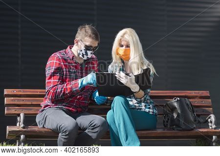 The Male And Female Colleagues With Face Mask And Protective Gloves Are Sitting On Bench And Working