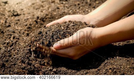 Young Women With Dirty Hands Holding Fertile Ground In Backyard Garden. Concept Of Growth, Environme