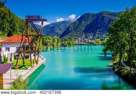 Lake With Wooden Diving Tower In The Slovenian Mountains In Front Of Blue Sky. High Quality Photo. C