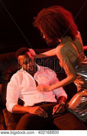 African American Woman In Dress Seducing Man In Formal Wear On Black