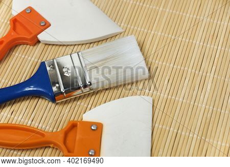 Classic paint brush with white bristles and blue handle. Rubber trowel with orange handle