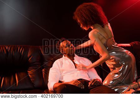 Curly African American Woman In Dress Seducing Man In Formal Wear Sitting On Sofa On Black