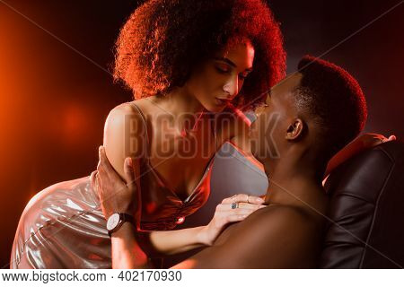 Curly African American Woman In Dress Seducing Shirtless Man On Black Background