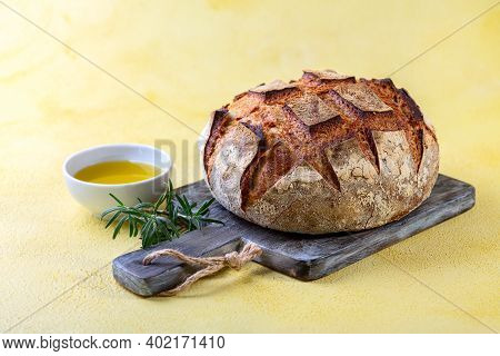 Artisanal Organic Sourdough Bread Olive Oil And Fresh Rosemary On A Textured Background With A Copy