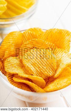 Crispy potato chips in bowl on white table.