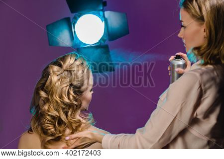 Stylist makes girl's hair, hair spray. Combing female hair. Hair care for woman. Stylist makes an evening hairstyle for model at photo shoot applies hairspray.