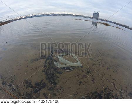 Ecology of Ukraine. Trash near the Dnepr River in Ukrainian capital. Environmental contamination. Illegal junk dump. December 27, 2020 Kiev,Ukraine