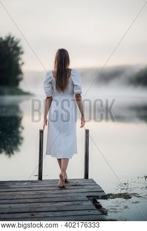 Back View Of Young Woman In White Dress Standing Alone On Footbridge And Staring At Lake. Foggy Chil