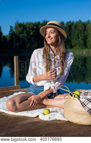Beautiful Young Woman Wearing Blue Shorts, Shirt And Hat Enjoys Her Morning Picnic On A Wooden Pier