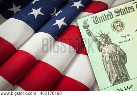 United States IRS Stimulus Check Resting on American Flag.