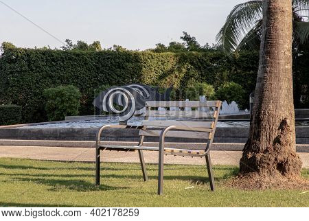 Bangkok, Thailand - Jan 06, 2021 : Wooden Benches On Grass Floor In A Shady Area Of The Park. Seatin