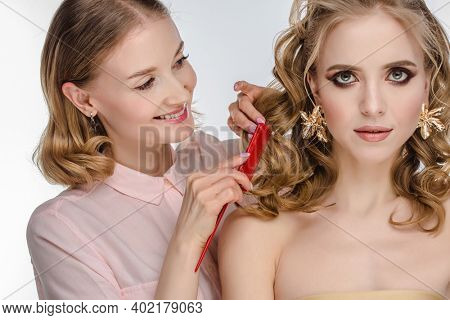 Stylist makes girl's hair. Combing female hair. Hair care for woman. Stylist makes an evening hairstyle for model at photo shoot.