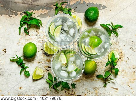Cocktail Margarita . Fresh Cocktail With Lime, Ice And Mint On A Rustic Background . Top View