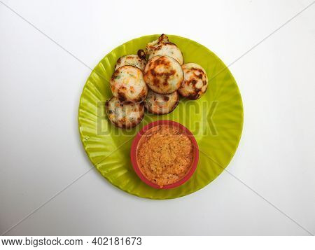 Paddu Or Kuzhi Paniyaram And Coconut Chutney In A Green Plate Isolated On White Background. Indian D