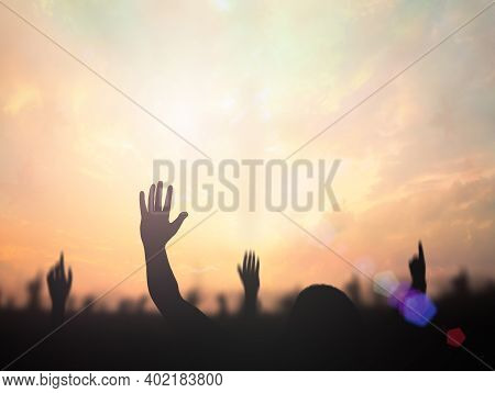 Worship God Concept: Silhouette Christian People Hand Rising Over Blurred Cross On Spiritual Light B