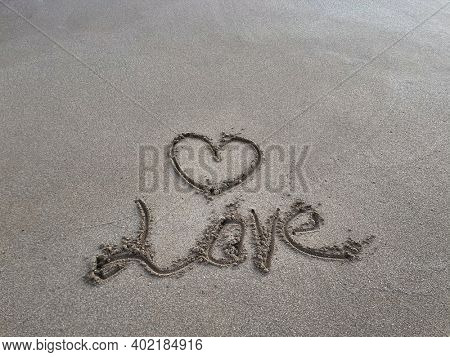 heart is drawn in the sand. Beach background. Top view