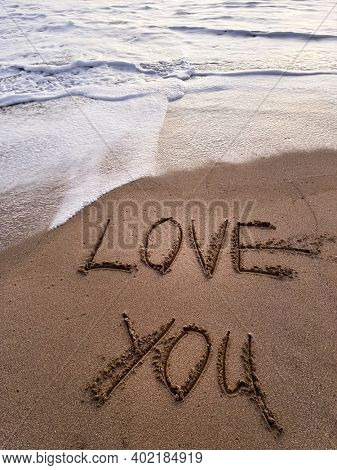 Love you is drawn on the sand. Beautiful view on the waves