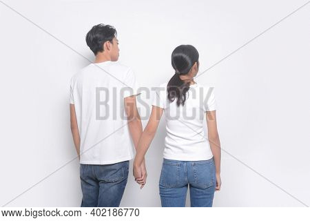 Romantic couples in love meet, hold hands, Loving couple posing back view on a white background. Relationship concept.