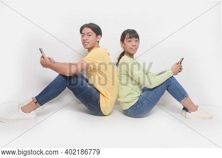 Couple sitting back to back and using phones