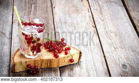 Cocktail Currants . A Cocktail Of Wild Currant With Ice On A Wooden Table. Free Space For Text.