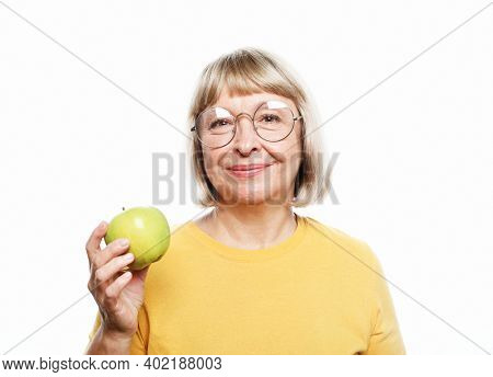 Food, health and old people concept: Portrait of senior woman holding an apple by her mouth over white background