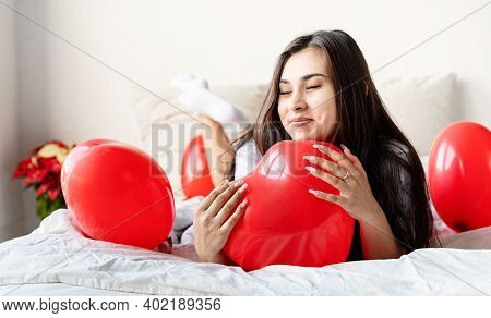 Young Happy Brunette Woman Laying In The Bed With Red Heart Shaped Balloons