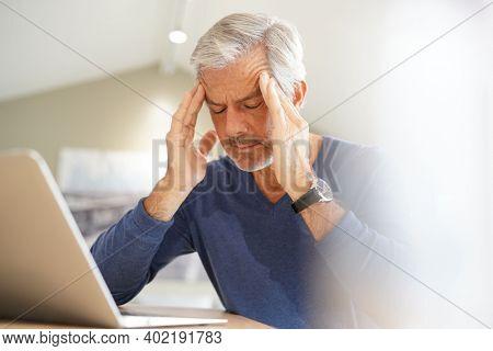 Senior man having a headache while working on laptop computer