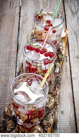 Cocktail Currants . Three Wild Currant Cocktail With Ice On A Wooden Table.