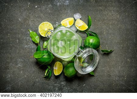 Lime Background. The Juice From The Limes With Ice And Sliced Limes Around . On The Stone Table. Top