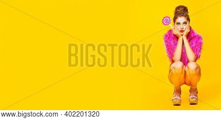 Glamorous fashionable girl posing with paper fuchsia lollipop and in fuchsia fur coat on a bright yellow background. Copy space. Beauty and cosmetics.