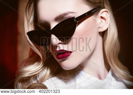 Glasses for women. A portrait of a beautiful confident lady with blonde hair wearing elegant sunglasses. Fashion and beauty.