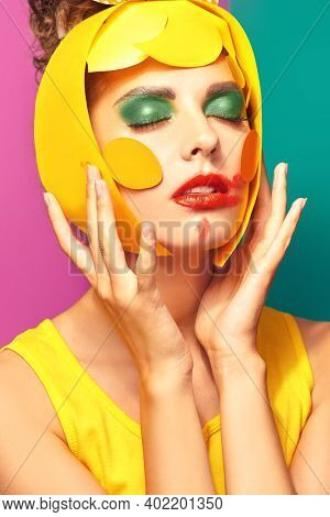 Bright style. Close-up portrait of a fashionable beauty girl with colorful paper makeup and hairstyle on a fuchsia and green background. Party style. Makeup and cosmetics.