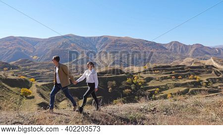 Lovely Young Couple Runs Along Hill Crest With Dry Grass Against Cascade Slope With Rare Yellow Tree