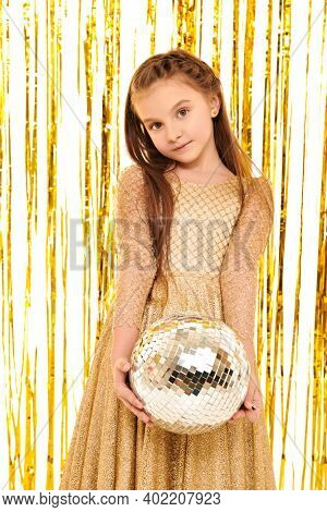 Kid's fashion and holidays. Beautiful child girl in a golden evening dress posing with disco ball on a background with shiny gold foil curtains. Children's party.