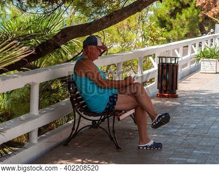 Sochi, Russia - 2 August 2019. Man Rests On A Bench On The Embankment Of Sochi.