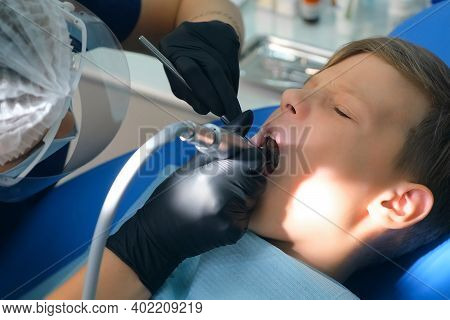 Dentist Hygienist Making Oral Hygienic Cleaning In Dentistry For Teen Child Boy, Face Closeup. Using